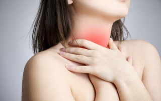 woman with acid reflux grasping throat in San Antonio TX
